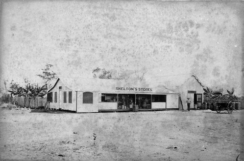 Corner of Smith and Bennett Streets, Palmerston 1875 - man standing in front of Skelton's Stores